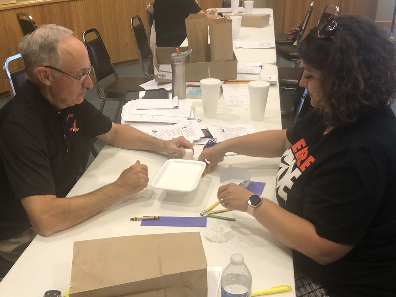 BOE member Mike Miller and teacher leader Erica Wright work on a creative activity.